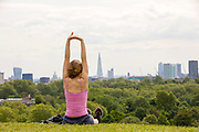 UNITED KINGDOM, London: 22 May 2019 <br /> Student Filipa Machado, 28 from Brazil, enjoys the warm weather in front of London's skyline on Primrose Hill today. The warm weather is set to continue reaching up to temperatures of 22 C in the capital tomorrow.<br /> Rick Findler / Story Picture Agency