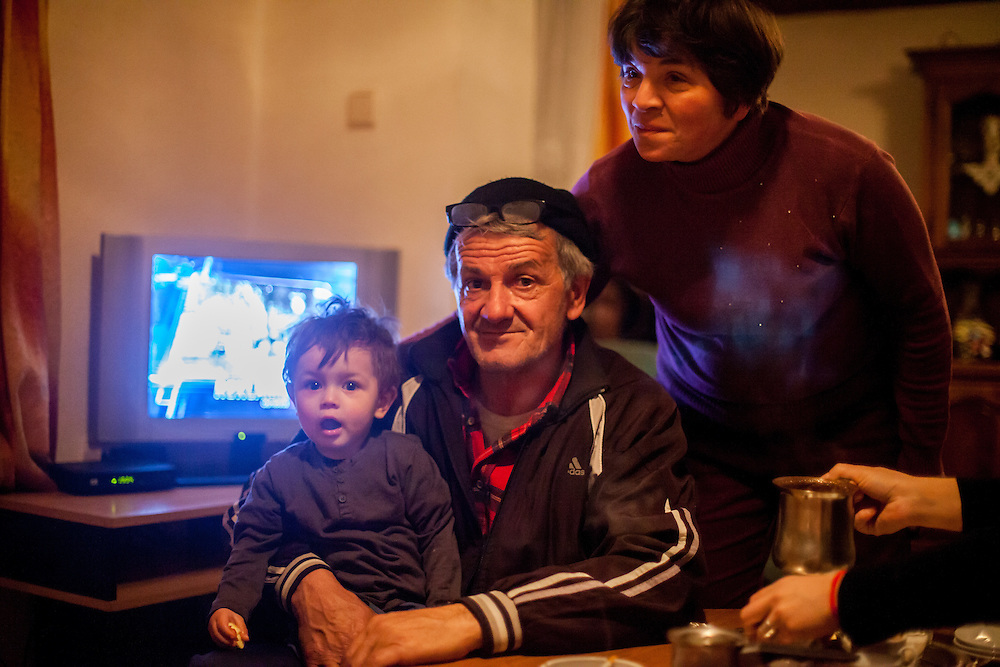 The parents of former refugee Elvis Causevic - father Nedzib (holding grandson Aldin (1 1/2)) and mum Dzevada - in the kitchen at the  families house in Hadžići. The family settled here after the war ended in Bosnia. Hadžići is a town and a municipality located about 20 km south west of Sarajevo city but within the Sarajevo Canton of Bosnia and Herzegovina. According to the census of 2013, Hadžići municipality has a population of 23,891 residents.