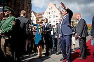"""Neurenberg - Koning Willem-Alexander en koningin Maxima tijdens een rondje Neurenberg. Het koningspaar brengt een tweedaags werkbezoek aan de Duitse deelstaat Beieren met als doel de goede relatie tussen Nederland en Beieren te versterken. koningin een mantel van Claes Iversen. Koning Willem-Alexander en koningin Maxima bij Justitiepaleis Neurenberg en Saal 600, waar de processen van Neurenberg na afloop van de Tweede Wereldoorlog hebben plaatsgevonden NEURENBERG - Koning Willem-Alexander en koningin Maxima sluiten hun werkbezoek af in het voormalig werk- en woonhuis van de Neurenbergse schilder Albrecht DŸrer (1471-1528). Het koningspaar brengt een tweedaags werkbezoek aan de Duitse deelstaat Beieren met als doel de goede relatie tussen Nederland en Beieren te versterken.  De grijze mantel uit de """"8-pieces"""" collectie is gemaakt in een double face. Het is hand geborduurd met kristallen, pailleten, ijzeren schroeven, bouten, moertjes en plexiglas elementen. De collectie is een ode aan de oude couture, ambacht en vakmanschap. De combinatie van couture silhouetten met moderne materialen en bewerkingen, maakt de collectie toch heel modern. Door toevoeging van constructieve ijzerwaren elementen wordt een referentie gemaakt naar het belang dat Claes Iversen hecht aan constructie en vakmanschap. copyright robin utrecht"""