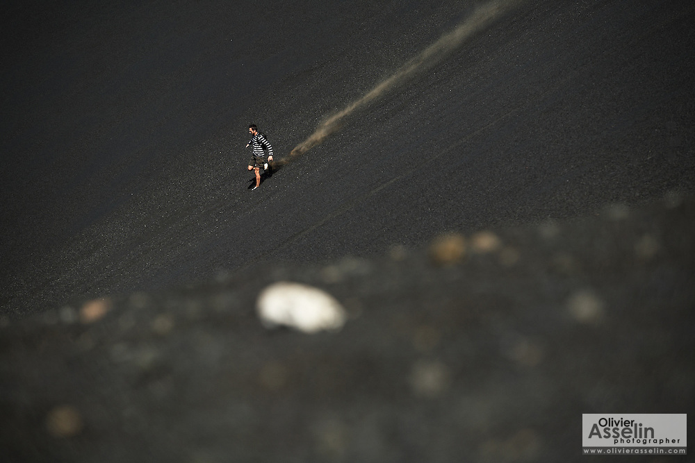 Man running down the slope of Pico Fogo, Fogo Island, Cape Verde, West Africa.