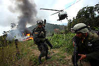 A member of the Jungla, a unit of the Colombian anti-narcotics police, signals in the landing for a Blackhawk helicopter after destroying a drug lab in a coca field in the Colombian state of Bolivar, on July 3, 2007. (Photo/Scott Dalton)