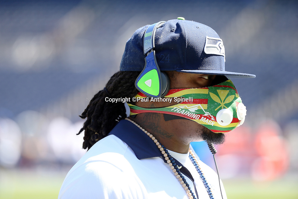 Seattle Seahawks running back Marshawn Lynch (24) walks around the field wearing a training mask while warming up before the 2015 NFL preseason football game against the San Diego Chargers on Saturday, Aug. 29, 2015 in San Diego. The Seahawks won the game 16-15. (©Paul Anthony Spinelli)