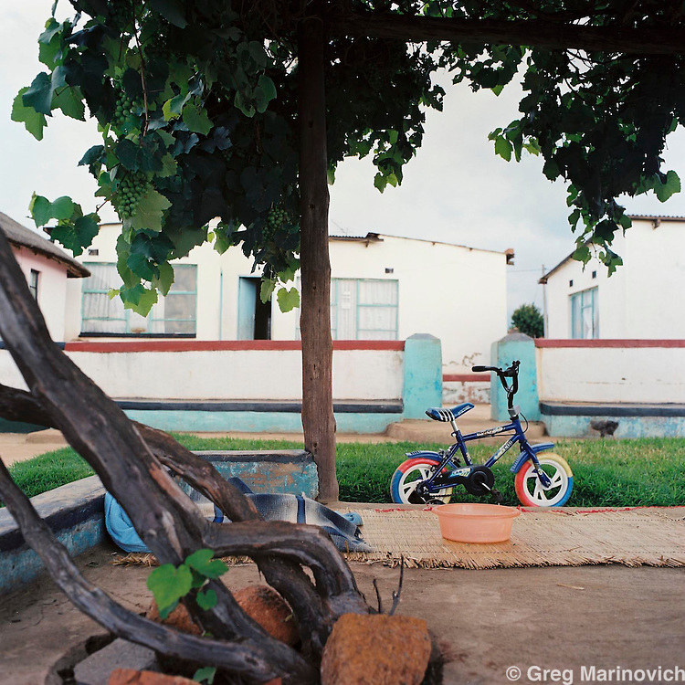 A child's bike under a grape arbour at a typical Ndebele style homestead prior to a storm in Mpumalanga, Nov 2008. Photo Greg Marinovich