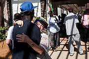 BANJUL, GAMBIA - JAN 18: A tourist hugs a local man outside the Palma Rima hotel after the British Government changed the travel advise to amber  due to the state of emergency issued by Gambian President Jammeh on January 18, 2017 in Banjul, Gambia.