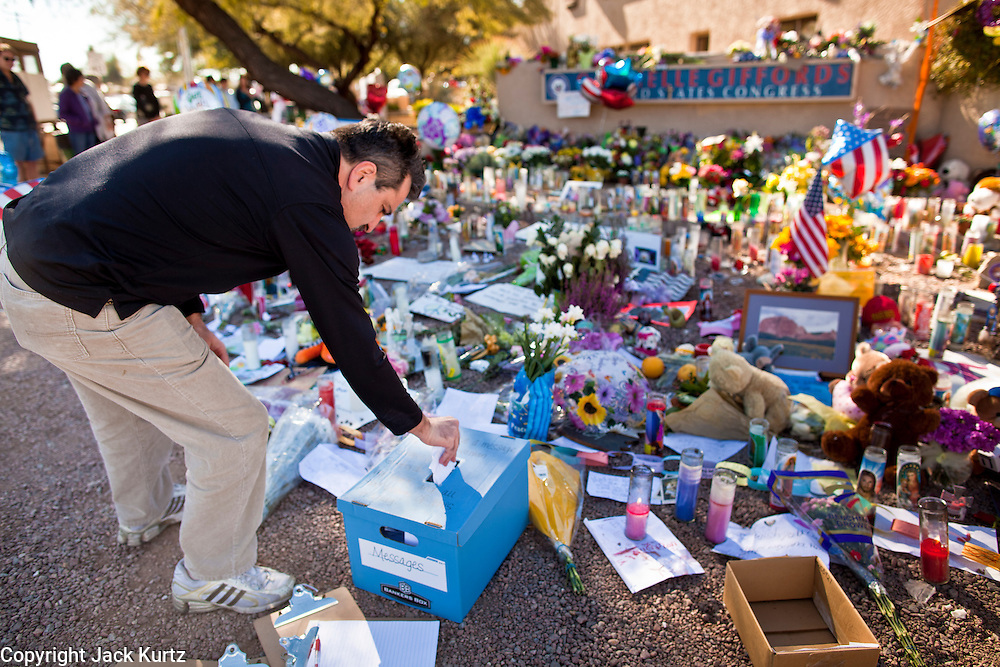 "15 JANUARY 2010 - TUCSON, AZ:  A man leaves a note for Congresswoman Gabrielle Giffords at a memorial at her office in Tucson, AZ, Saturday, January 15. Six people were killed and 14 injured in the shooting spree at a ""Congress on Your Corner"" event hosted by Arizona Congresswoman Gabrielle Giffords at a Safeway grocery store in north Tucson on January 8. Congresswoman Giffords, the intended target of the attack, was shot in the head and seriously injured in the attack but is recovering. Doctors announced that they removed her breathing tube Saturday, one week after the attack. The alleged gunman, Jared Lee Loughner, was wrestled to the ground by bystanders when he stopped shooting to reload the Glock 19 semi-automatic pistol. Loughner is currently in federal custody at a medium security prison near Phoenix.      PHOTO BY JACK KURTZ"