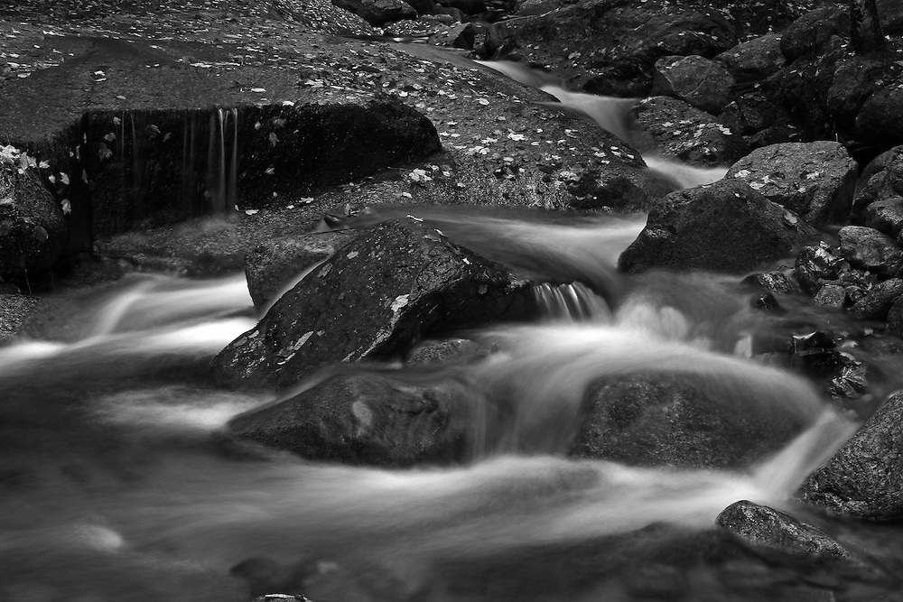 This intimate landscape photography image of Flume Brook at Franconia Notch State Park near Lincoln in the New Hampshire White Mountains region features silky water tumbling down the creek during New England fall foliage season. Table Rock is a small section of Conway granite in this New Hampshire State Park that was exposed and outcropped of hundreds of years. This scenic New Hampshire cascading water section is 500 feet long and 75 feet wide.<br /> This NH B&amp;W landscape photography image is available as museum quality photography prints, canvas prints, acrylic prints or metal prints. Black and white photography fine art prints may be framed and matted to the individual liking and decorating needs:<br /> <br /> http://juergen-roth.pixels.com/featured/flume-brook-at-franconia-notch-state-park-nature-juergen-roth.html<br /> <br /> All photographs are available for digital and print image licensing at www.RothGalleries.com. Please contact me direct with any questions or request.<br /> <br /> Good light and happy photo making!<br /> <br /> My best,<br /> <br /> Juergen<br /> Prints: http://www.rothgalleries.com<br /> Photo Blog: http://whereintheworldisjuergen.blogspot.com<br /> Twitter: @NatureFineArt<br /> Instagram: https://www.instagram.com/rothgalleries<br /> Facebook: https://www.facebook.com/naturefineart