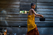 A local boy inside the Ankor Wat grounds takes a pot of hot water back to his home.