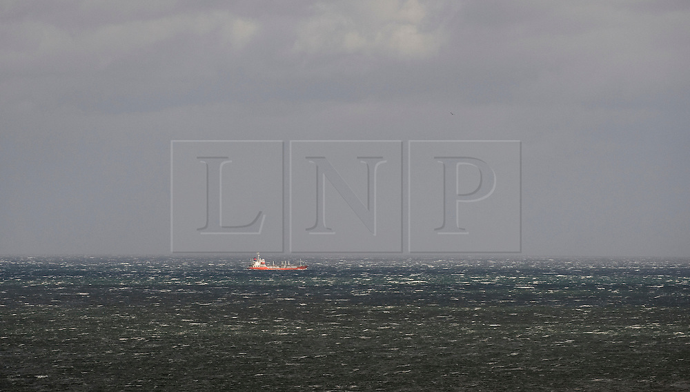 © Licensed to London News Pictures. 12/09/2011..Saltburn Beach, Saltburn, Cleveland, England...Strong winds blow across the beach at Saltburn in Cleveland as a ship makes its way through choppy seas...Photo credit : Ian Forsyth/LNP