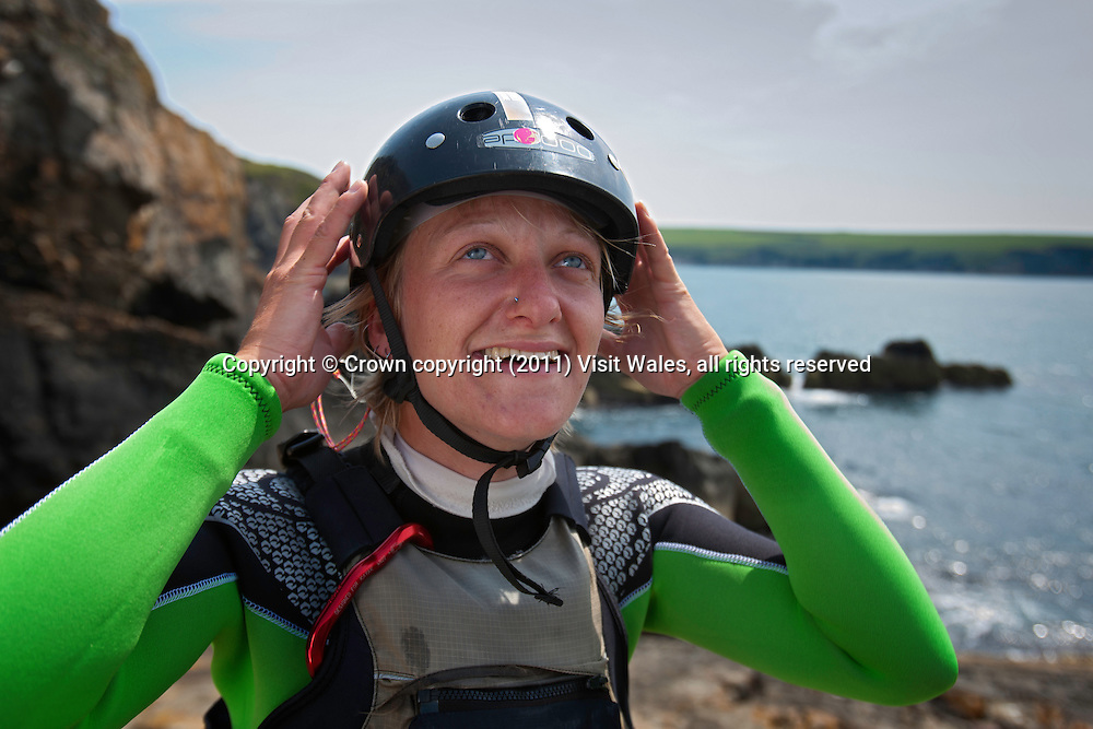Woman putting on helmet<br /> Coasteering<br /> North Pembrokeshire<br /> South<br /> Activities and Sports