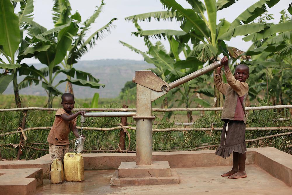 Sisters Janet Uwimana 4 and Marie Chantal Uwitonze 3 operated a water pump installed by Water Aid. Juru Sector. Bugesera district. Rwanda...© Zute Lightfoot / Water Aid