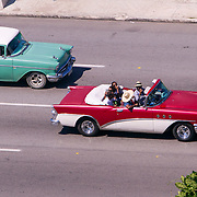 Old classic cars on Havana's famous coastal drive El Malecon, some cars carry tourists others are the everyday transportation for Cubans as seen from the Hotel Nacional.  Photography by Jose More