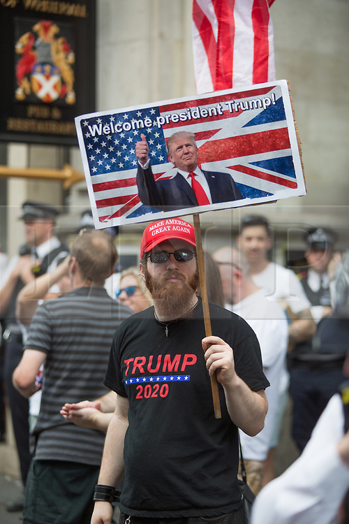 @Licensed to London News Pictures 13/07/2018. London, UK. A  Pro-Trump demonstrator stands alone on the streets of Central London. Demonstrators march through the streets of Central London in protest to the US President Donald Trump' visit to the UK.Photo credit: Manu Palomeque/LNP