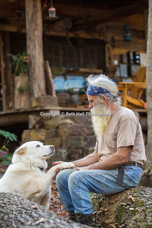 Robert Runyan sits with his dog Athena outside of his home in Sugar Tree Hollow in Winslow, Arkansas, for Out Here Magazine. Photo by Beth Hall