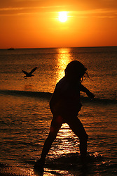 Silhouette of little girl wading in the surf at sunset