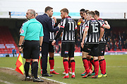Grimsby Town Manager Michael Jolley talks to his players whilst the match was stopped because of crowd trouble during the EFL Sky Bet League 2 match between Grimsby Town FC and Port Vale at Blundell Park, Grimsby, United Kingdom on 10 March 2018. Picture by Mick Atkins.