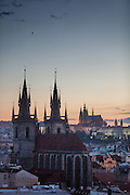 View to the Prague cityscape and the towers of Tyn Church located at Old Town Square. On the right Prague Castle and St. Vitus Cathedral during sundown.