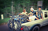 A group of young mountain bikers shuttle to the top of Brockway Mountain in the back of a truck in Copper Harbor Michigan.