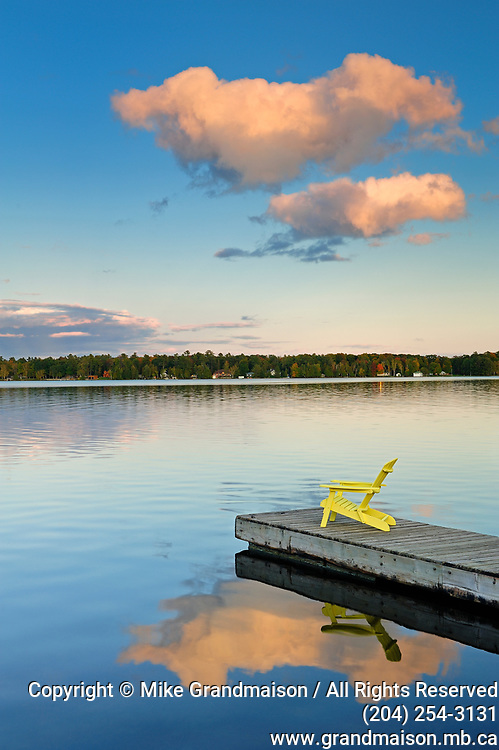 Clouds reflected in Silent Lake with Muskoka chair on dock<br />