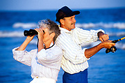 Senior couple surf fishing and sightseeing at the beach