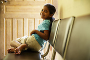 A young girl sits on a bench at the health center in the town of San Esteban, Honduras on Wednesday April 24, 2013.