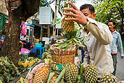 06 JUNE 2013 - BANGKOK, THAILAND:     Vendors cut up pineapple to sell in Bobae Market in Bangkok. There is also a fresh fruit section of the market. Bobae Market is a 30 year old market famous for fashion wholesale and is now very popular with exporters from around the world. Bobae Tower is next to the market and  advertises itself as having 1,300 stalls under one roof and claims to be the largest garment wholesale center in Thailand.       PHOTO BY JACK KURTZ