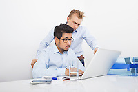 Businessmen using laptop together at desk in office