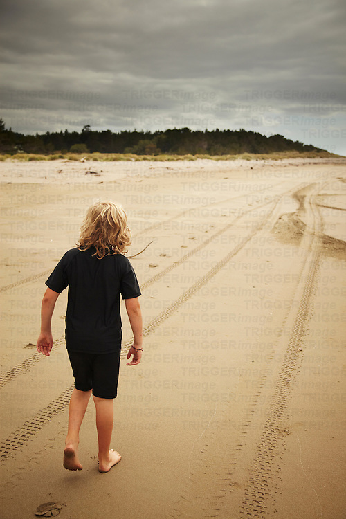A young boy walking along a deserted beach with tire tracks