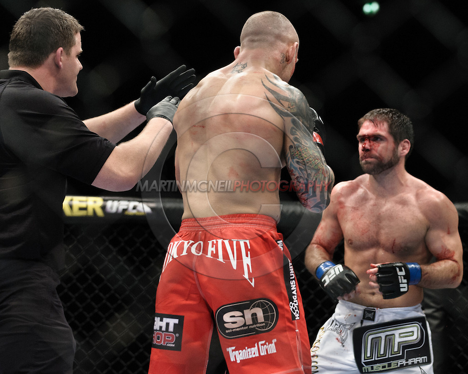 "MANCHESTER, ENGLAND, NOVEMBER 14, 2009: The referee calls a time out after Aaron Riley (facing) sustained a cut from a strike by Ross Pearson during ""UFC 105: Couture vs. Vera"" inside the MEN Arena in Manchester, United Kingdom."