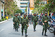 "01 FEBRUARY 2014 - BANGKOK, THAILAND: Thai soldiers walk into a polling place to secure it early Sunday morning. Security at many polling places was provided by the Thai army. Thais went to the polls in a ""snap election"" Sunday called in December after Prime Minister Yingluck Shinawatra dissolved the parliament in the face of large anti-government protests in Bangkok. The anti-government opposition, led by the People's Democratic Reform Committee (PDRC), called for a boycott of the election and threatened to disrupt voting. Many polling places in Bangkok were closed by protestors who blocked access to the polls or distribution of ballots. The result of the election are likely to be contested in the Thai Constitutional Court and may be invalidated because there won't be quorum in the Thai parliament.    PHOTO BY JACK KURTZ"