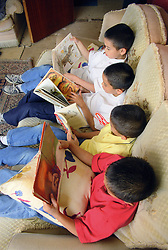 Group of twin boys sitting on sofa reading story books,