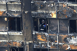 Fire service personnel survey the damage to Grenfell Tower in west London after a fire engulfed the 24-storey building on Wednesday morning.