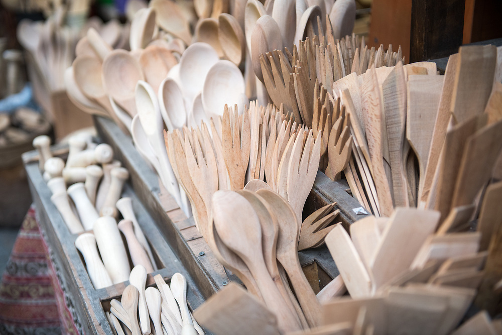 Wooden kitchen utensils laid out in bins at outdoor marketplace, Istanbul, Turkey.