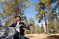 Senior woman riding motorcycle through a forest