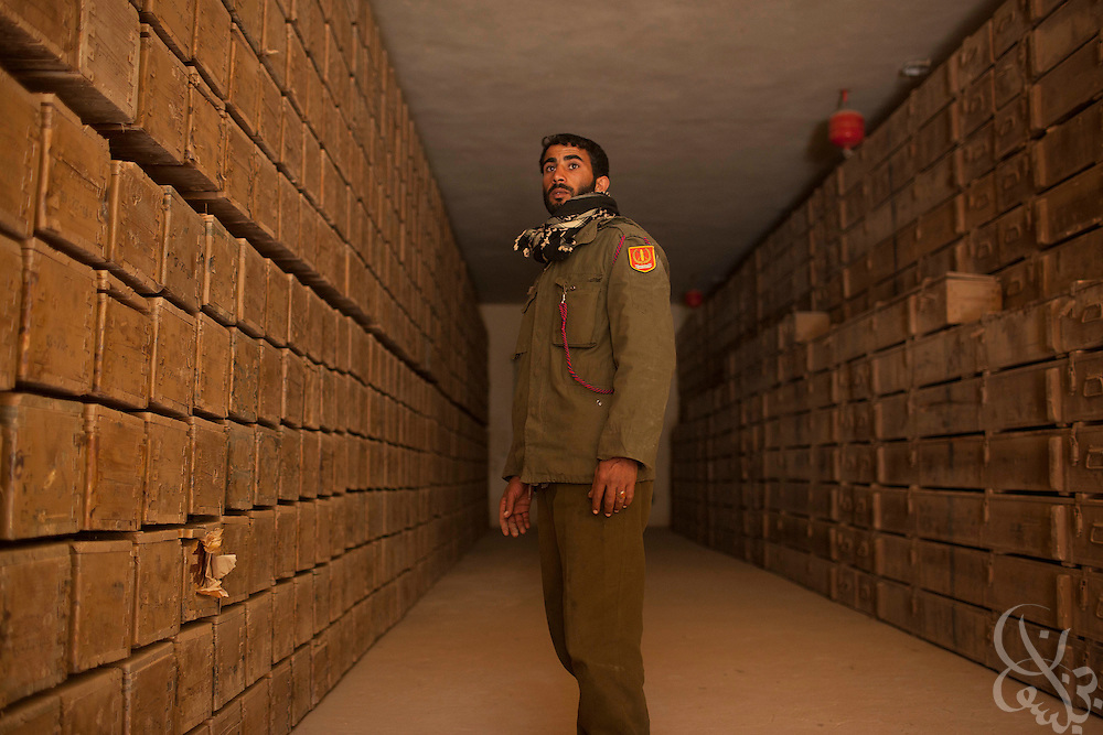 A Libyan opposition fighter walks through a bunker containing hundreds rockets and crates of ammunition March 1, 2011 at an opposition ammunition depot near the eastern Libyan city of Ajdabiya. Opposition forces are reported to have repelled Pro-Qaddafi attempts to take back at least three cities around Tripoli today. .Slug: Libya.Credit: Scott Nelson for the New York Times