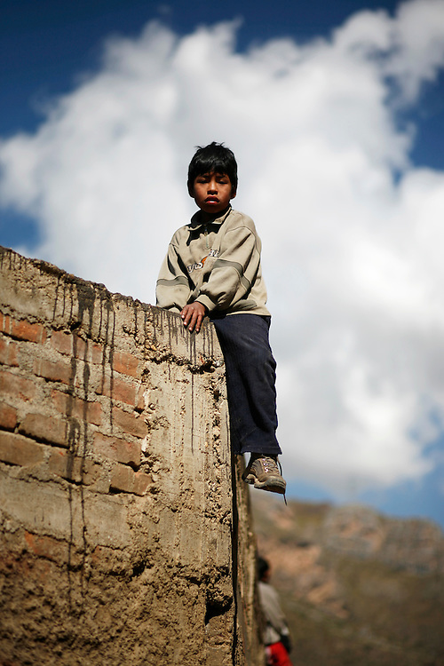 A young boy sits atop a wall surrounding the main arena where bulls were gathered for auction in Huancavelica, Peru (lat -12.7667°, long -74.9833°, Alt. 13,060 Ft.), Friday, May 16, 2008. .