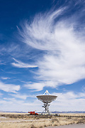 "Swirling cirrus clouds over Very Large Array (VLA) radio astronomy telescope, near Socorro, New Mexico, USA. The Karl G. Jansky Very Large Array (VLA) is one of the world's premier astronomical radio observatories. Visit the VLA on the Plains of San Agustin fifty miles west of Socorro, between the towns of Magdalena and Datil, in New Mexico, USA. US Route 60 passes through the scientific complex, which welcomes visitors. The VLA is a set of 27 movable radio antennas on tracks in a Y-shape. Each antenna is 25 meters (82 feet) in diameter. The data from the antennas is combined electronically to give the resolution of an antenna 36km (22 miles) across, with the sensitivity of a dish 130 meters (422 feet) in diameter. After being built 1973-1980, the VLA's electronics and software were significantly upgraded from 2001-2012 by at least an order of magnitude in both sensitivity and radio-frequency coverage. The VLA is a component of the National Radio Astronomy Observatory (NRAO). Astronomers using the VLA have made key observations of black holes and protoplanetary disks around young stars, discovered magnetic filaments and traced complex gas motions at the Milky Way's center, probed the Universe's cosmological parameters, and provided new knowledge about interstellar radio emission. The VLA was prominently featured in the 1997 film ""Contact,"" a classic science fiction drama film adapted from the Carl Sagan novel, with Jodie Foster portraying the film's protagonist, Dr. Eleanor ""Ellie"" Arroway, a SETI scientist who finds strong evidence of extraterrestrial life."