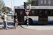 Een stadsbus blokkeert fietsers de doorgang, terwijl zij groen licht hebben..<br /> <br /> A city bus is blocking the way for cyclist at a traffic light.