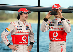"""© London News Pictures. 31/01/2013 . Woking, UK.  Jenson Button (right) using his mobile phone to photograph photographers and the media. Team McLaren Mercedes drivers Jenson Button and Sergio """"Checo"""" Perez unveil the new MP4-28 Formula 1 car at the McLaren Technology Centre in Woking, Surrey, UK on  Thursday, Jan. 31, 2013. Photo credit : Ben Cawthra/LNP"""