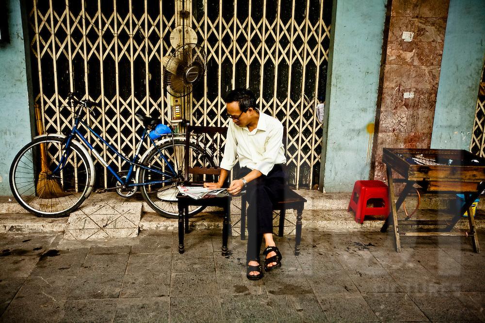 A Vietnamese man reads a newspaper in a street of Hanoi, Vietnam, Southeast Asia