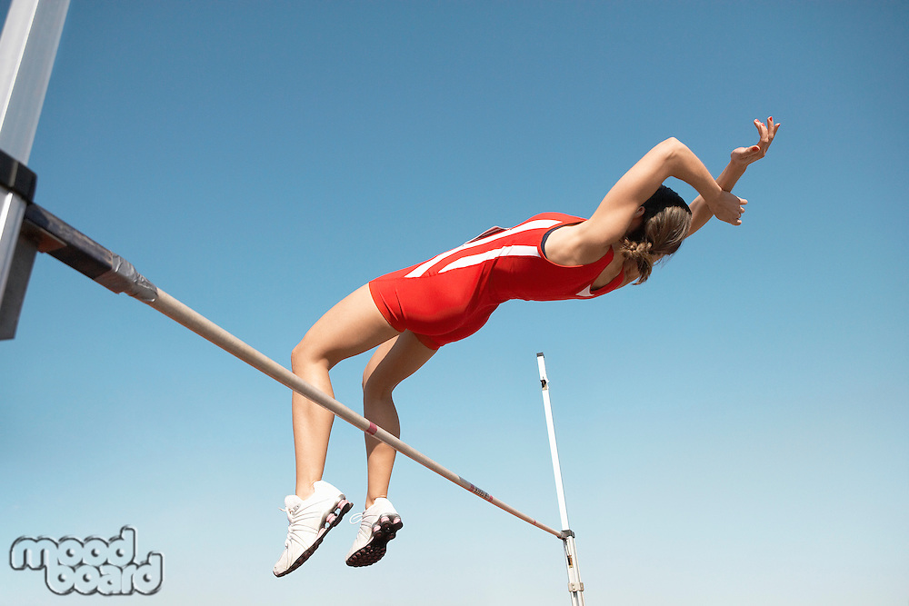 High Jumper in mid air over bar view from below