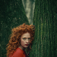 Female youth with curly red hair leaning onto a tree.