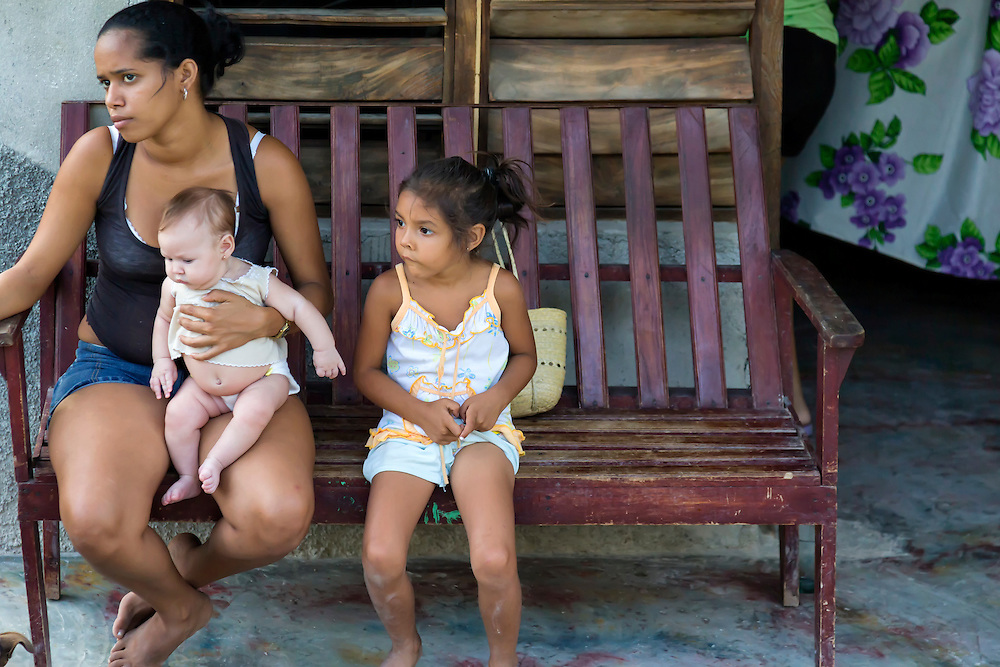 Woman with her children on their porch in Charco Redondo, Granma, Cuba.