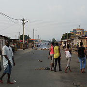 Locals wander the streets of Niykabiga in Bujumbura, moments after the National Police moved in to the area to disperse a group of protestors who blocked the road to prevent a candidate from a political party aligned with the ruling party CNDD-FDD, to rally in neighbourhood.