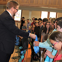 Amory First United Methodist Church Pastor Wesley Pepper, left, distributes bags of school supplies to students of the congregation following a prayer for their safety and success during the new school year. The church included a blessing of the backpacks with its Sunday service.