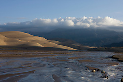 Medano Creek flows along side the dune field with the Sangre di Cristo mountains hiding in cumulous clouds.  Great Sand Dunes National Park and Preserve contains the tallest sand dunes in North America. The Dunefield, topping off with Star Dune at 750 feet, is created by sand trapped by the nearby Sangre de Christo Mountains (larger rougher grains and pebbles) and the San Juan Mountains (65 miles to the west).  Waterways such as Medano Creek help carry the sediment down to the San Luis valley where the dunes are found. Great Sand Dunes National Park and Preserve, Mosca, Colorado.