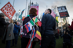 © Licensed to London News Pictures. 13/03/2017. London, UK. A woman wrapped in flags joins protestors gathered in Parliament Square to defend EU migrants' right to remain in the UK after Brexit.  Parliament is expected to pass the Brexit bill this week allowing the Prime Minister to trigger Article 50. Photo credit: Peter Macdiarmid/LNP