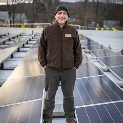 PV Squared employee Daniel Gomez at a solar panel installation on the roof of a commercial building in Greenfield, Massachusetts.
