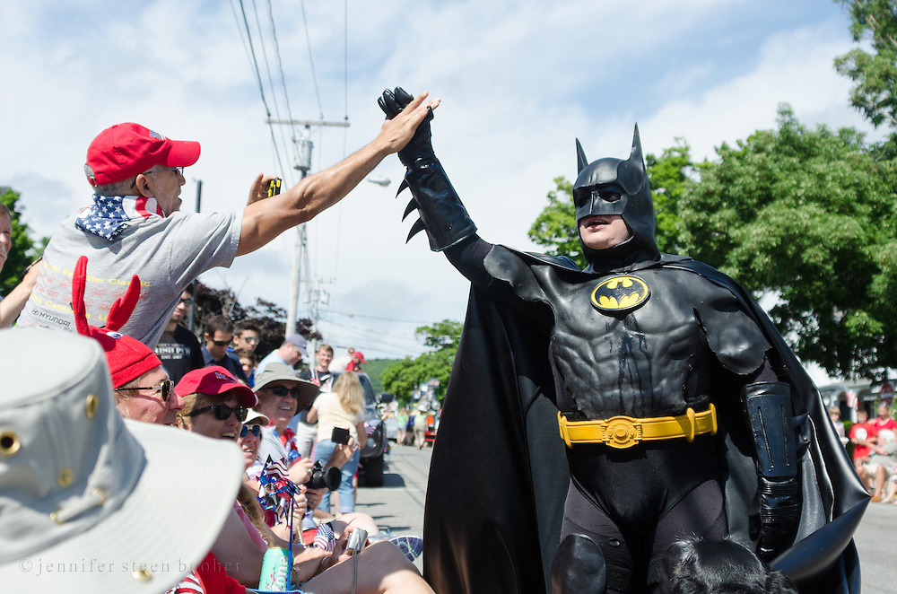 """BAR HARBOR, MAINE, July 4, 2014. """"Bar Harbor Batman"""" give a high-five to a spectator at the Independence Day Parade"""
