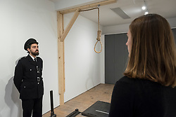 "© Licensed to London News Pictures. 13/11/2018. LONDON, UK. Staff members, one posing as a prison guard, view a hangman's noose.  Preview of ""Glad I Did It"", a new work by Irish artist Christina Reihill at Bermondsey Project Space.  The interactive artwork looks at the life and death of Ruth Ellis, the last woman to be hanged in Britain, after she shot her lover, racing driver, David Blakely in 1955.  On display are the artist's interpretation of Ruth Ellis' prison cell, including furniture and props, the hanging room together with a video display of the artist in conversation.   The show runs 14 November to 1 December 2018.  Photo credit: Stephen Chung/LNP"