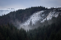 © Licensed to London News Pictures . 12/12/2014 . Blackpool , UK . Morning mist rises through the forests of the Peak District in Derbyshire towards snow-capped hills , as viewed from the Snake Pass road in the Peak District between Manchester and Sheffield . Photo credit : Joel Goodman/LNP